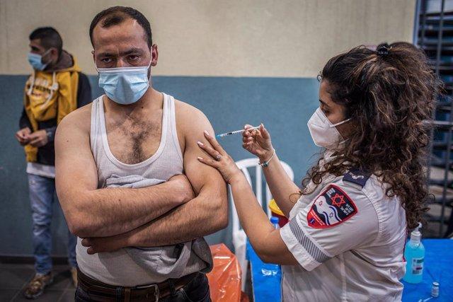 Archivo - Arxivo - Un treballador palestí amb permís de treball a Israel rep una dosi de la vacuna contra el coronavirus