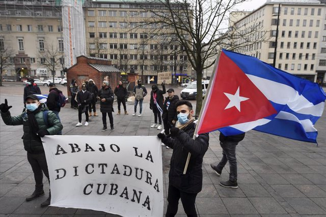 Archivo - 05 December 2020, Finland, Helsinki: Cubans hold a banner during a protest against the Cuban government's human rights violations in front of the Cuban Embassy. Photo: Vesa Moilanen/Lehtikuva/dpa