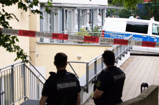 Archivo - 04 June 2021, Saxony, Dresden: Police officers stand behind a barrier in front of a student dormitory in the Dresden district of Strehlen. After the death of a returnee from India who had contracted COVID-19, all residents of the high-rise build
