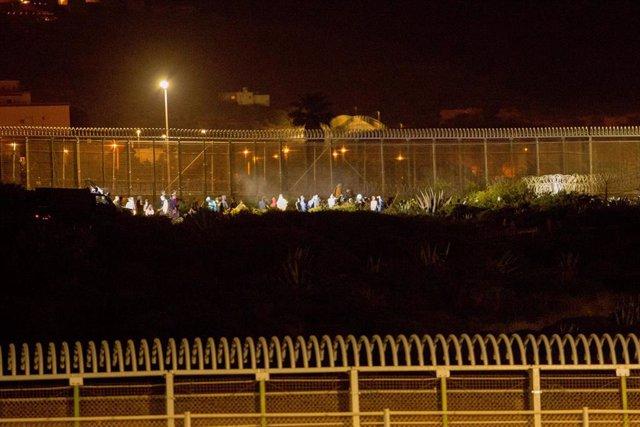 Archivo - Varios marroquíes intentan llegar a suelo español desde la frontera que separa Melilla y Marruecos, en una imagen de archivo