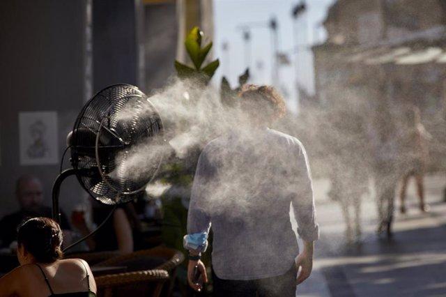 Un hombre camina al lado de un difusor de vapor de agua de un restaurante de la calle Alcalá, a 2 de julio de 2021, en Madrid, (España).