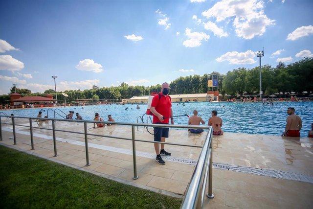 Un hombre desinfecta las zonas de la piscina del Parque Deportivo de Puerta de Hierro, el primer día de apertura de las piscinas para la temporada de verano, a 26 de junio de 2021, en Madrid (España).