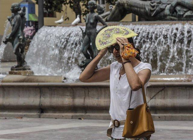 Una mujer se tapa la cabeza con un abanico para guarecerse de las altas temperaturas cerca de una céntrica fuente en València