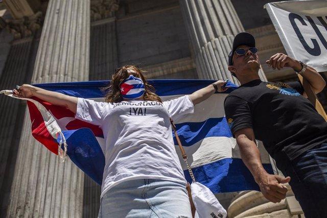 Varias personas se concentran sosteniendo banderas en el Congreso de los Diputados en apoyo a las movilizaciones contra el Gobierno cubano registradas ayer en la isla, a 12 de julio de 2021, en Madrid (España)