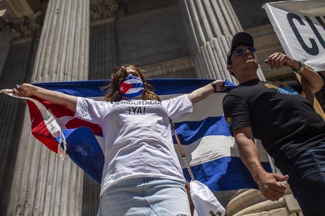 Diverses persones es concentren sostenint banderes al Congrés dels Diputats en suport a les mobilitzacions contra el Govern cubà registrades ahir a la illa, a 12 de juliol de 2021, a Madrid (Espanya)
