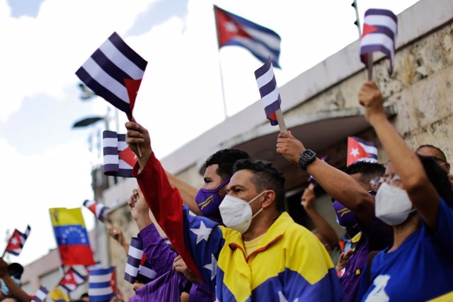 12 July 2021, Venezuela, Caracas: A woman waves flags of Venezuela and Cuba during a rally in front of the Cuban Embassy in support of the island's government. Scores of people had demonstrated the day before in Havana and several other Cuban cities again