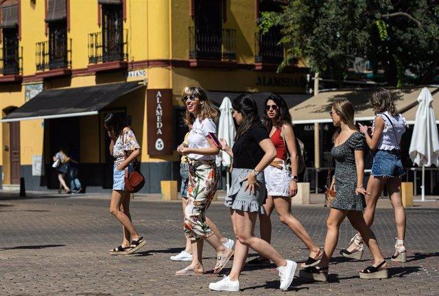 Un grupo de jóvenes sin mascarilla pasean por la Alameda de Hércules, durante el primer día en el que no es obligado el uso de la mascarilla en exteriores desde el inicio de la pandemia, a 26 de junio de 2021, en Sevilla (Andalucía), España. El 30 de marz