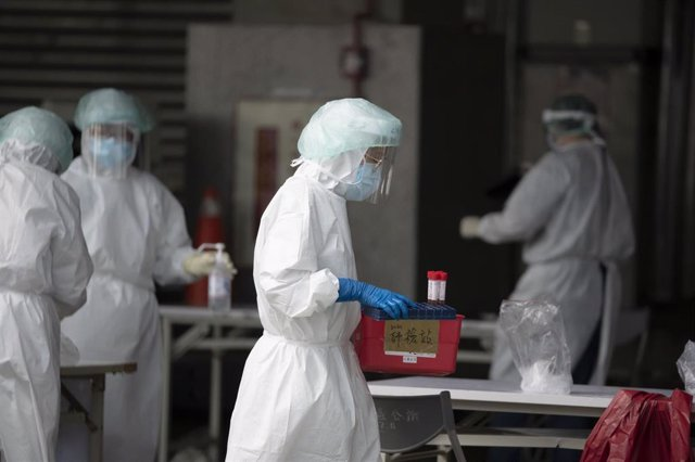 03 July 2021, Taiwan, Taipei: A medical worker wearing protective equipment carries a tray with PCR samples at a testing station in Huannan Nan Market, where Coronavirus infections are significantly rising. Photo: Brennan O'connor/ZUMA Wire/dpa