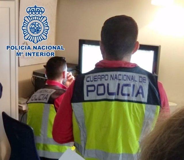 Archivo - Dos agentes de Policía Nacional en una investigación