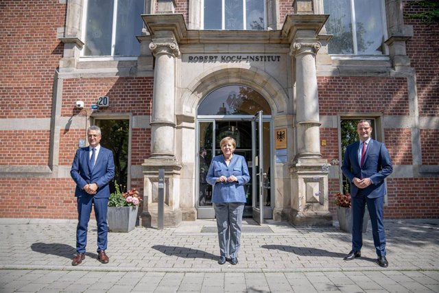 13 July 2021, Berlin: German Chancellor Angela Merkel (C), Germany's Health Minister Jens Spahn (R) and President of the Robert Koch Institute (RKI), Lothar Wieler pose for a picture in front of the entrance to the RKI. Photo: Michael Kappeler/dpa-pool/dp
