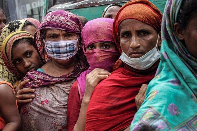 Bangladeshíes esperan en una cola al reparto de comida por parte del Gobierno durante la pandemia de COVID-19.