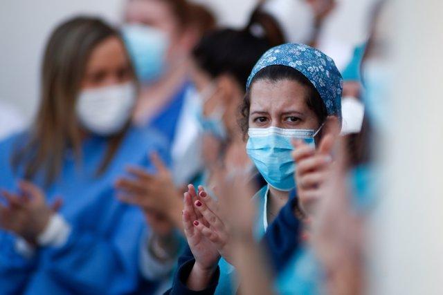 Varios sanitarios aplauden a Fuerzas y Cuerpos de Seguridad durante el homenaje diario a los sanitarios en el Hospital Infanta Elena de Valdemoro como consecuencia de la pandemia de coronavirus en Valdemoro, Madrid, España, a 13 de abril de 2020.
