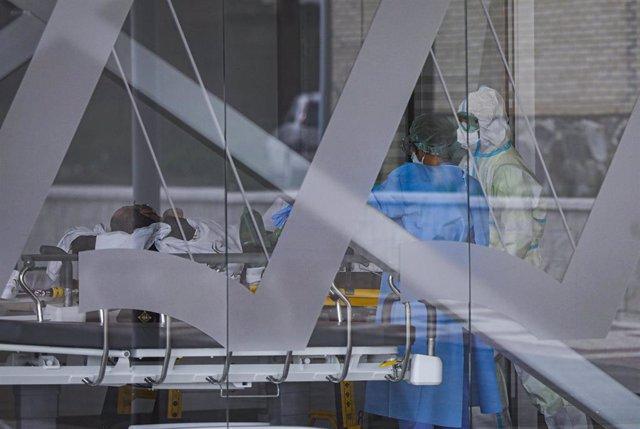 Archivo - Sanitarios con traje EPI durante el ingreso de un paciente covid-19 al nuevo Hospital de Emergencia Covid-19. En Sevilla (Andalucía, España), a 01 de febrero de 2021.(Foto Archivo)