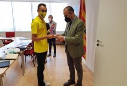 El atleta aragonés Eduardo Menacho, muestra al consejero de Educación, Cultura y Deporte, Felipe Faci. El oro que ha logrado en la prueba de 10.000 metros en el Campeonato de Europa sub23.