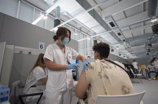 Un joven recibe la primera dosis de la vacuna xxxx en el Hospital Zendal el día que comienza la vacunación a jóvenes madrileños a partir de 16 años, a 13 de julio de 2021, en Madrid (España).