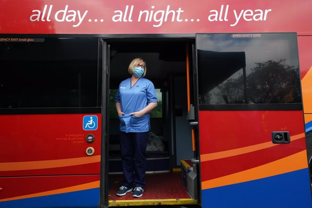 02 July 2021, United Kingdom, Crieff: Vaccination Nurse Lesley Cousland waits for a patient onboard a bus in the car park of Crieff Community Hospital. The bus is being used by the Scottish Ambulance Service as a mobile vaccination centre where the vaccin