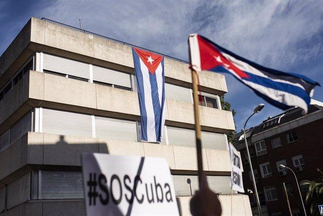 Varias personas se concentran ante la Embajada de Cuba en Madrid en contra del Gobierno cubano.