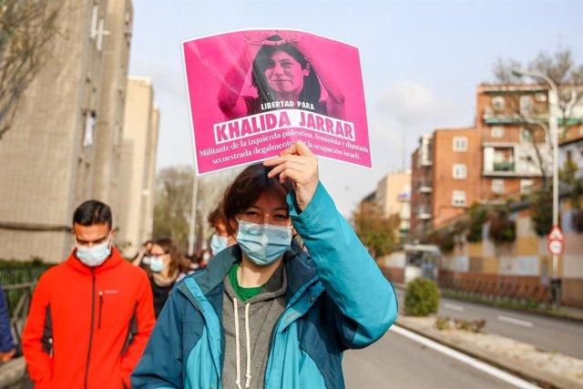 Archivo - Una mujer con un cartel en el que se lee: `Libertad para Khalida Jarrar durante una marcha y batukada feminista en el barrio de Lucero, en Madrid (España), a 5 de marzo de 2021. Esta marcha feminista con motivo del día de la Mujer, el próximo 8