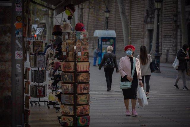 Archivo - Arxivo - Una dona enfront d'una botiga d'articles turístics a Barcelona, Catalunya (Espanya)