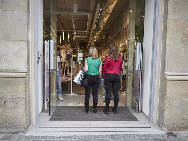 Archivo - Dos mujeres en la puerta de una tienda de ropa en Pamplona.