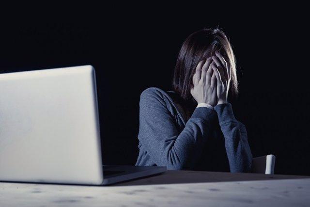 Archivo - Una adolescente refleja una situación de acoso delante de un ordenador