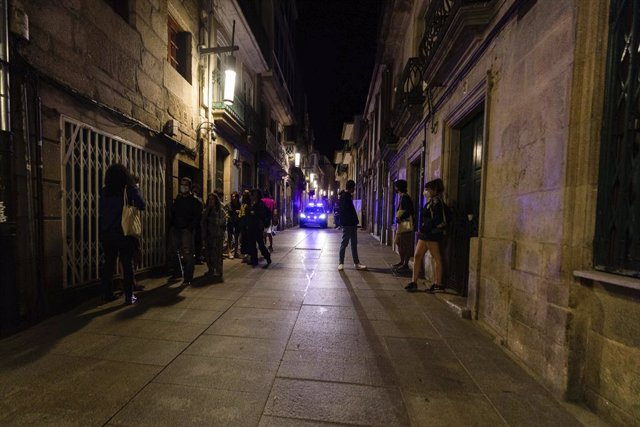 Un coche de policía pasa frente a varias personas en ambiente festivo, a 10 de julio de 2021, en Pontevedra, Galicia (España). El ocio nocturno en Galicia vive este fin de semana su segunda reapertura al público. Esta medida solo se produce en municipios