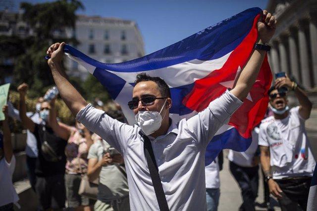 Un hombre sujeta la bandera de Cuba durante una concentración en las inmediaciones del Congreso de los Diputados en apoyo a las movilizaciones contra el Gobierno cubano registradas ayer en la isla, a 12 de julio de 2021, en Madrid (España).