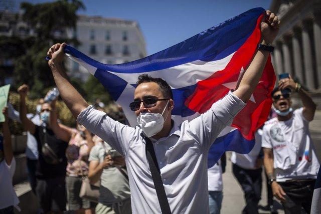 Un hombre sujeta la bandera de Cuba durante una concentración en las inmediaciones del Congreso de los Diputados en apoyo a las movilizaciones contra el Gobierno cubano registradas ayer en la isla, a 12 de julio de 2021, en Madrid (España). Convocada por