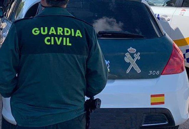 Archivo - Un agente de la Guardia Civil de espaldas y junto a un vehículo oficial del cuerpo.