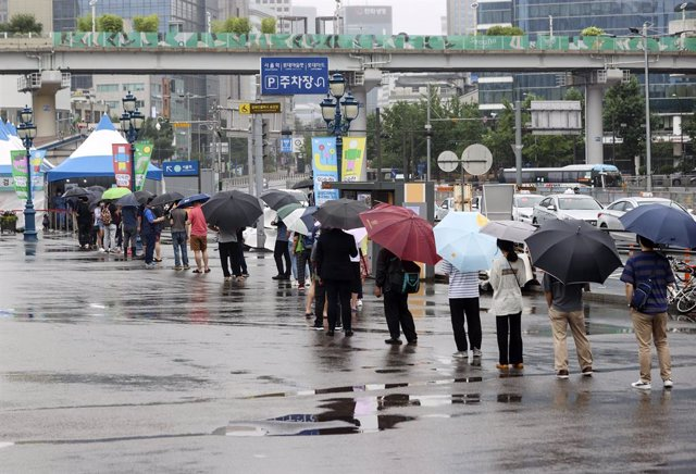 04 July 2021, South Korea, Seoul: People wait in line to be tested for the coronavirus at a temporary testing site set up outside Seoul Station. Photo: -/YNA/dpa