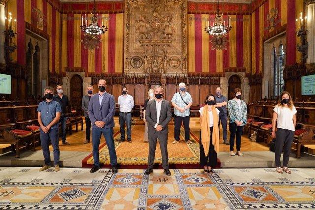 El primer tinent d'alcalde, Jaume Collboni, al costat del comissionat Álvaro Porro i representants de l'economia social i solidària i dels grups municipals
