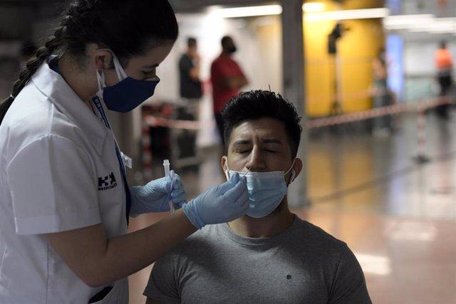 Una sanitaria realiza un test de antígenos a un hombre, en un dispositivo de realización de test de antígenos en el intercambiador de Plaza de Castilla, a 2 de julio de 2021, en Madrid (España).
