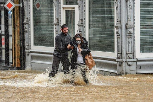 14 July 2021, Belgium, Spa: A man helps a woman to cross a flooded street amid heavy rains. Photo: Bruno Fahy/BELGA/dpa