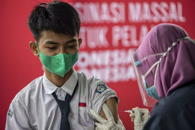 14 July 2021, Indonesia, Tangerang: A healthcare worker injects a child with a dose of a coronavirs vaccine during a mass vaccination campaign for school children aged 12 to 17 years at State Junior High School 11 South Tangerang.