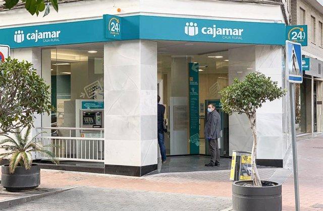 Archivo - Un cliente entra en una oficina de Cajamar en Motril durante el estado de alarma por el Covid-19.