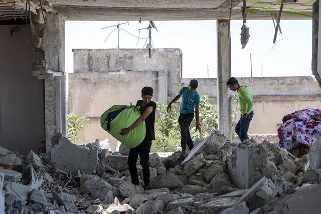 Varios niños recuperan bienes de su vivienda tras un ataque del Ejército de Siria contra la provincia de Idlib