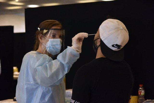 Una trabajadora sanitaria realiza un test de antígenos a un joven para acceder al primer día del festival Cruïlla, a 8 de julio de 2021, en Barcelona, Cataluña, (España).