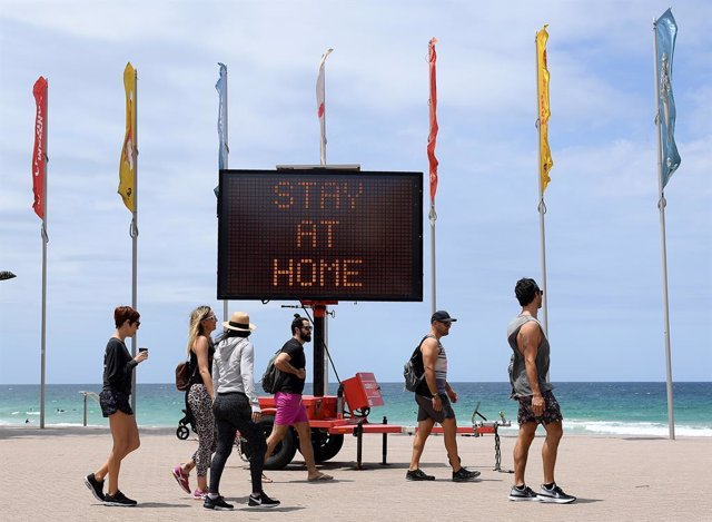 """Archivo - 26 December 2020, Australia, Sydney: People walk in front of an electronic board written on it """"Stay at Home"""" on the empty Manly beach. Sydney's northern beaches remain under New South Wales Government (NSW) ordered lockdown as the Government tr"""