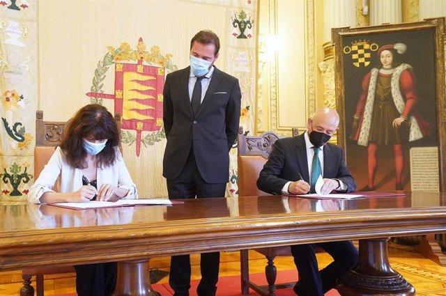 El director de Relaciones Institucionales y Grupos de Interés, Fernando Ríos; y la concejal de Cultura del Ayuntamiento, Ana Redondo, firman el acuerdo de colaboración en presencia del alcalde de la ciudad, Óscar Puente.