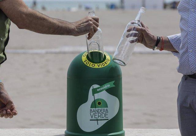 Dos personas tiran una botella de vidrio en uno de los contenedores que simbolizan el inicio de la campaña de verano 'Movimiento Banderas Verdes: campaña por una recuperación verde en la hostelería', en el Paseo Marítimo de València.