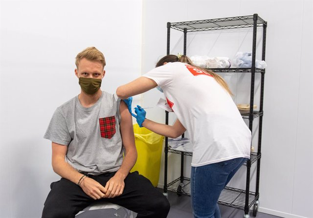 25 June 2021, United Kingdom, London: A man is injected with a dose of Coronavirus vaccine at a Covid-19 vaccination centre in the Emirates Stadium, the football stadium of the English premier league club Arsenal FC. Photo: Dominic Lipinski/PA Wire/dpa