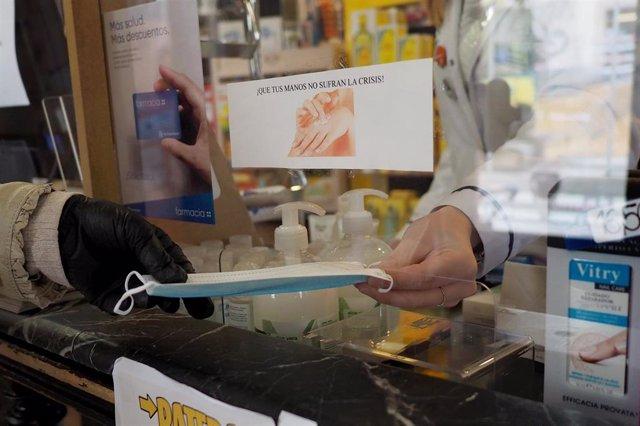 Archivo - Una persona coge una mascarilla que le da una trabajadora de una farmacia de Vitoria