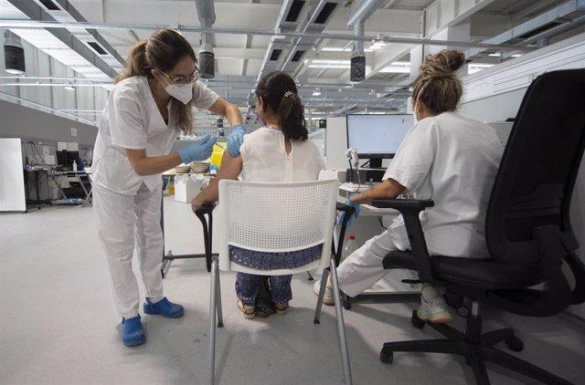 Una joven recibe la primera dosis de la vacuna Pfizer en el Hospital Zendal el día que comienza la vacunación a jóvenes madrileños a partir de 16 años, a 13 de julio de 2021, en Madrid (España).