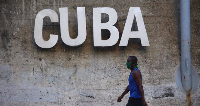 Archivo - 30 April 2020, Cuba, Havana: A man wearing a face mask walks past a sign reading 'CUBA'. Labour Day Parade has been cancelled in Cuba amid the coronavirus pandemic. Photo: Guillermo Nova/dpa