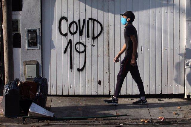 Archivo - Un hombre con mascarilla por el coronavirus en una calle de Buenos Aires