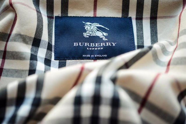 """Archivo - FILED - 12 March 2014, Bavaria, Bamberg: The label with the logo of the fashion designer """"Burberry London"""" in a trench coat. The British fashion group Burberry has cancelled its previous forecasts for its business results this fiscal year, and w"""