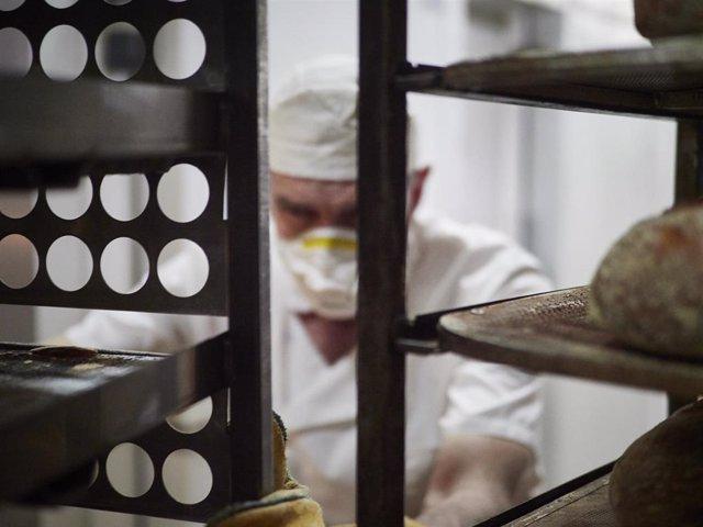 Archivo - Un trabajador protegido con mascarilla maneja bandejas para cocer pan, foto de recurso