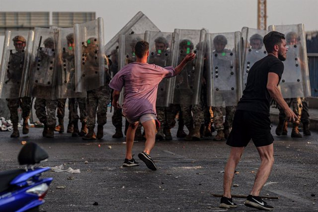 15 July 2021, Lebanon, Beirut: A protestor hurls rocks at Lebanese soldiers during clashes after Lebanon's Prime Minister-designate Saad Hariri stepped down following his failure to form a government for nearly nine months. Photo: Marwan Naamani/dpa