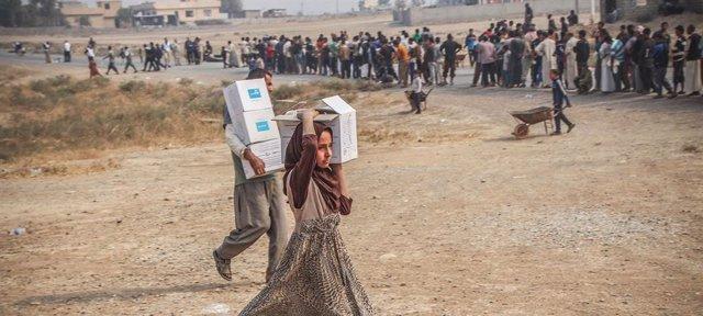 Archivo - Trabajadores humanitarios distribuyendo ayuda de emergencia en la localidad iraquí de Ibrahim Jalil