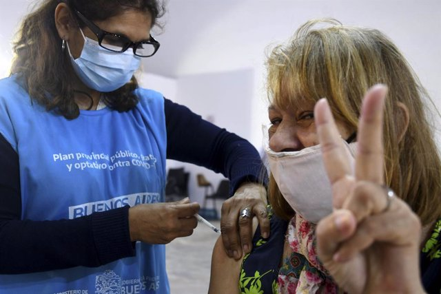 Archivo - 20 April 2021, Argentina, Buenos Aires: A woman makes the victory sign while receiving a Covid-19 vaccine in Buenos Aires province. Photo: ---/telam/dpa